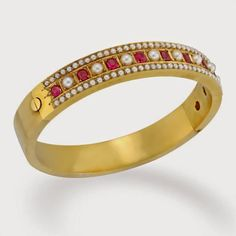 MID-VICTORIAN RUBY AND PEARL BANGLE, ca. 1860, the bangle set with a central row of ten oval-shaped faceted rubies, estimated to weigh a total of 1.70 carats, alternately set with nine pearls, measuring approximately 3-3.2 mm in diameter, all four claw-set within square yellow gold mounts, a row of 41 half seed pearls to each side, all to a wide square-section yellow gold bangle with hinged fitting, gross weight 20.6 grams, circa 1860