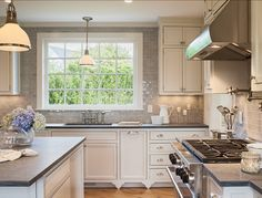 "The countertops are honed ""Pietra de Cardoza granite"", a harder alternative to soapstone. The tile is a custom color (seafoam-ish) 2″x4″ subway porcelain with a hand-applied glaze by ""Mexican Handcrafted Tile Inc."" Lighting above island is the ""Randolph Pendant from Hudson Valley Lighting""."