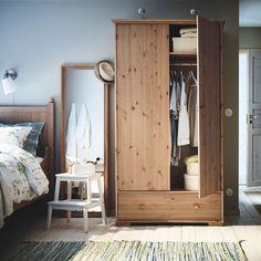 Un dormitorio con armario y cama HURDAL de pino macizo, y un espejo STABEKK con marco de madera maciza