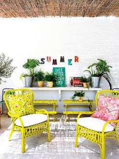 A fun seating area decorated with yellow chairs and benches, white shelf with pots, artwork, and a white rug