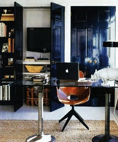 Designed by Nate Berkus for His Home. Home Office Space in a small space used closet for media center & home office supplies. Glass table being used for the desk.Nate Burkus' Apartment in New York City. 500 Square foot studio apartment.