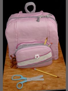 This fondant covered cake took three 12 in square cakes divided in half and one 8 in square for the front pocket.   The teddy bear, pencils, and scissors are fondant.  The board is a foam board covered in fondant and painted to look like the top of a school desk.