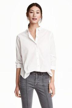 Chemise en coton: Chemise à manches longues en coton tissé. Modèle droit avec col rabattu et fermeture par boutons nacrés devant. Un peu plus de longueur dans le dos.
