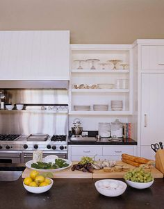 A Chef's Dream kitchen for Ina Garten. Open shelves are stocked with a collection of cake stands and hotel silver. Viking range and hood; Sub-Zero refrigerator; Bosch dishwasher; KitchenAid mixer.