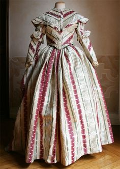 A beautiful dress and matching pelerine dating to 1843, but made of recycled late-18th century material.