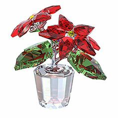 Poinsettia. The leaves of the Poinsettia in faceted Light Siam and Peridot crystal with accents in Light Topaz crystal reflect the colors of Christmas. It thrives in its fully faceted clear crystal flowerpot.