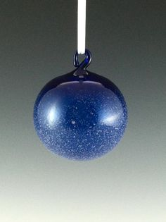 This is a cobalt blue ornament with specks of white on the surface. The white glass is applied to surface when it is in a molten state just
