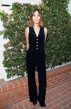 Alexa Chung wears a corduroy vest, flares, and black boots