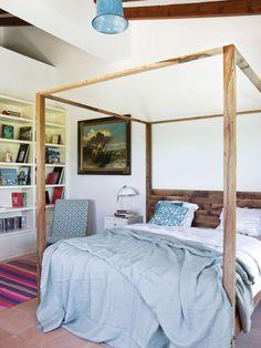 cama con dosel con ropa de cama abierta en tonos blancos y azules