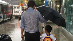 Priorities: See 'umbrella dad' get all wet to keep his son dry