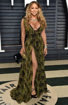 Mariah Carey flashes her cleavage in plunginganimal-print gown #dailymail