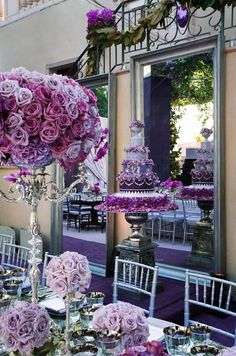 A magnificent cake on a metallic pedestal featured tiers of purple ombré frosting that incorporates the hues of fresh roses nearby.