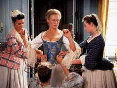 Glenn Close as the Marquise de Merteuil being laced into stays in the movie Dangerous Liaisons.
