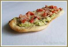 Avocado spread, shredded chicken, tomatoes and parmesan cheese on herbed flatbread