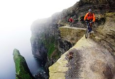 On The Edge Photograph Bicyclists Hans Rey and Steve Peat cross the famous Cliffs of Moher in Ireland, traversing through seemingly impossible trails on their bicycles.