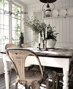 Charming country dining ... painted dining table base with stained plank top. Metal chairs. Painted paneling. And those wonderful windows. Whens lunch?