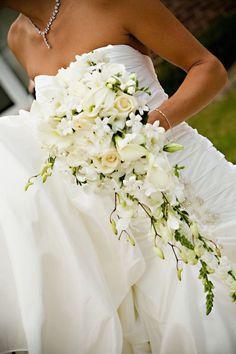 Un ramo de novia de orquídeas en cascada con alcatraces, orquídeas dendrobium y rosas fotografiado por The princess parlour.