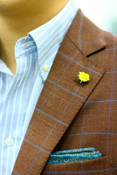 Carrying one color throughout an outfit can be too matchy-matchy. But mixing patterns (patterned pocket square on windowpane jacket on striped shirt) prevents this. And the yellow lapel pin adds such a cool pop.