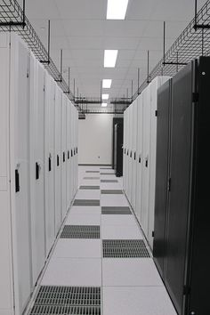 Data center cold aisle configuration, note perforated floor panels to direct cold air to server cabinets.