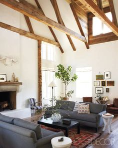The living area of Patrick Printy and Dan Holland's house in Sonoma County includes a pair of custom-made sofas upholstered in reversed black denim, a Jonathan Adler cocktail table, Oly side tables, a French armchair in vintage mattress ticking, and an antique rug; the walls are made of plaster, and the beams and dormer are of reclaimed oak.   - ELLEDecor.com