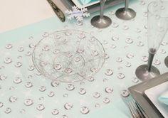 """Le chemin de table """"Emily"""" est décoré de petites bulles, qui ne sont pas sans rappeler celles d'un verre de champagne !   Il a été superposé à un chemin en intissé de couleur bleu clair."""