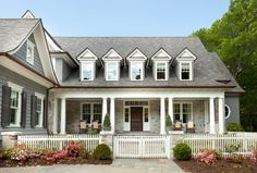 Front yard with picket fence. Picket fence. Traditional home with front porch and picket fence. #picketfence T.S. Adams Studio. Interiors by Mary McWilliams from Mary Mac & Co.