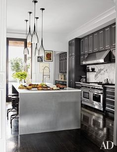 Holly Hunt pendant lights are suspended above the Caesarstone-top island in the kitchen, which is equipped with a Wolf range and hood | archdigest.com