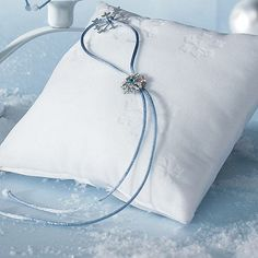 Accented by embossed snowflake designs, soft white velvet, and icy blue ribbons, the Winter Wonder snowflake ring bearer pillow adds subtle elegance to any winter wedding ceremony.