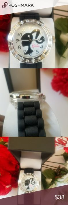 🌷🌷WOMENS BARBIE BLING WATCH🌷🌷 WOMENS BARBIE VINTAGE STYLE BING WATCH. THE DIAL IS SILVER BLACK AND WHITE WITH A LITTLE PINK. HAS A PICTURE OF BARBIE INSIDE. THE BAND IS ALL BLACK RUBBER. VERY NICE...BRAND NEW WITH TAGS.. Barbie Accessories Watches