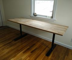 Make a beautiful butcher block table with IKEA hardwood countertop and IKEA desk frame.