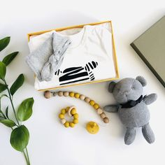 A very cute animal theme gift set suitable for a baby boy or baby girl. * White cotton romper with zebra print through the front and grey marl top knot hat. * Soft cotton knit bear with ribbon neck tie in Slate, measures 16cm from sitting. * Food grade silicone and beech wood pacifier clip and teether in Mustard. * All orders arrive beautifully gift wrapped in our Classic gift box (26x18x8cm). Re-use as a keepsake box. Romper White footless romper with full zebra print through the front for… Unisex Baby Gifts, Newborn Baby Gifts, Baby Gift Sets, Baby Arrival, Baby Prints, Top Knot, Keepsake Boxes, Zebra Print, Food Grade