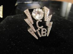 """Elvis Jewelry On Display At Graceland ~16-carat diamond """"TCB"""" ring Elvis often wore. The ring features a huge 11.5-carat diamond solitaire in the middle framed by two diamond lightning bolts. When he wore it while performing, Elvis would have to tape it to prevent fans from stealing it when he shook their hands. It cost about $35,000 in the 1970s, Kern explained to Knoxville.com."""