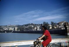 A civilian woman rides her bicycle across a bridge ( ponte Aleardi ) in Verona, Italy in 1944 or 1945 | The Digital Collections of the National WWII Museum : Oral Histories