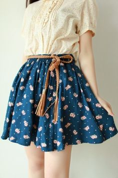 White blouse with a floral skirt and a brown waist belt