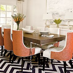 Heavy-textured chairs and a chevron stripe rug serve as the focal points in this glam dining room.