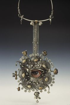"""ButtonArtMuseum.com - Eyeball Pendant 1998 / 7.5"""" x 6.25"""" x 1.5""""   (without hanging device) sterling silver, fine silver, eyeglass frame and lens, photo, Great Grandma Schertz's squash seeds, beach pottery, shell buttons, garnets, clock parts, plastic wrench, pearls, wire mesh, gold-plated sweater clip"""
