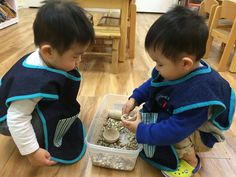 What's in your bowl brother?   Mixed age classrooms promote crossed-age learning. The older child is demonstrating his mastery of this work while the younger child is observing keenly and curiously. It also helps to boost the older child's confidence level.