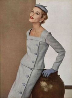 Givenchy 1955.  If you rid yourself of the pillbox hat, I think this could still be a very current look.  Love the buttons, love the slim silhouette and the square neckline.