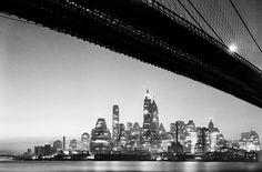 Baje el horizonte de Manhattan por la noche, visto por debajo del puente de Brooklyn, Brooklyn final en febrero de 1938. Ver esta escena hoy en este mapa de Google Street View . (EM Bofinger / Cortesía Archivo Municipal de Nueva York)