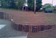 curved retaining wall from railway sleepers on end Cheap Retaining Wall, Sleeper Retaining Wall, Garden Retaining Wall, Landscaping Retaining Walls, Hillside Landscaping, Driveway Landscaping, Sloped Garden, Back Gardens, Outdoor Gardens