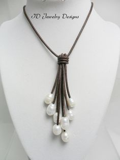 "Must have for every woman .Handmade dark Brown Leather white Rice Pearl Freshwater Pearl Cluster Necklace. 2mm dark brown genuine Leather cord ,8 Pearls 10-12mm in size white color, 18"" inches in length ,the Pearls drop are 4.5"" inches on the longest drop,button loop closure.  comes Gift Boxed..."