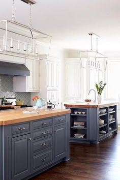 Fantastic kitchen features white perimeter cabinets paired with white marble countertops and a gray glass arabesque tile backsplash.