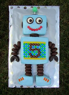 Robot Cake. No tutorial, but you can mostly see the different items I used. My Choices: - Candy Melt Covered Donut Hole for the Antenna, on a Stick - Halved Oreos for the Eyes - Junior Mint Pupils - Gum Drop Mouth - Little Debbie Chocolate Covered Mini Donut Arms / Legs - Entenmann's Chocolate Covered Mini Donuts for the Neck and the 'Claws' (they are a little bigger than the others) - Yellow Twizzler Borders - M&M's around number - Whoppers for the '5' - Mike & Ike Candy for the 'Laces'