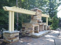 A large custom fireplace with pergola accents make for a great area for entertaining around the fire. By Signature Outdoor Concepts