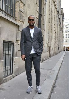 Shop this look on Lookastic: http://lookastic.com/men/looks/black-sunglasses-white-crew-neck-t-shirt-grey-suit-grey-athletic-shoes/8631 — Black Sunglasses — White Crew-neck T-shirt — Grey Suit — Grey Suede Athletic Shoes