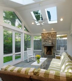 this screen porch addition features a ceiling fan and a fireplace so owners are able to cool down or warm up the place