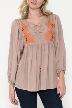 Bohemian long sleeve peasant blouse with flower embroidery and gold beading detail in the front. Wood beads string on collar. Content + Care: 100% Rayon Hand Wash