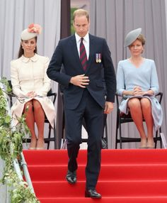 Prince William, Duke of Cambirdge walks down steps to give a speech as he is watched by Catherine, Duchess of Cambridge and Queen Mathilde of Belgium attend a 100 Years Commomoration Ceremony at Le Memorial Interallie on August 2014