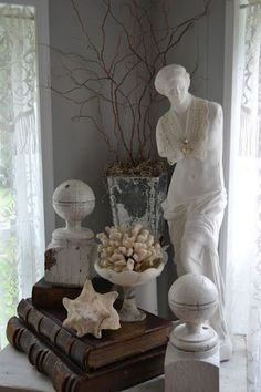 Beautiful display of books, shells and other collectibles in like colors. (A modest statue, I must say)
