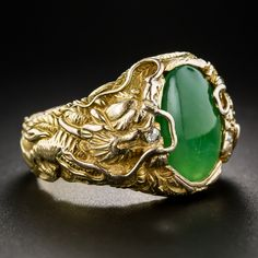 Chinese Jade Gent's Ring with Dragons. A shiny spinach green jadeite cabochon is closely guarded left and right by a pair of fierce Chinese dragons, each bearing a tiny twinkling diamond in its jaws. The artful repousse style details continue all around the size 9 1/4 ring shank. Exotically handsome.
